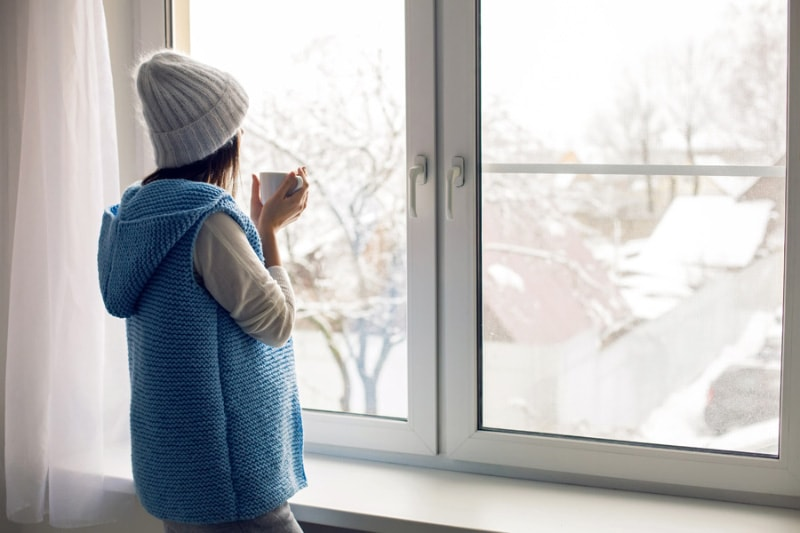 Woman In Winter Clothing Looking Out of Her Window
