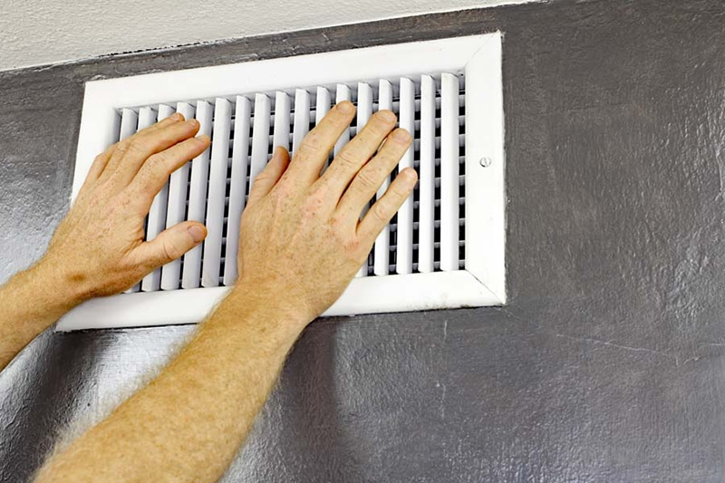 a pair of adult male hands feeling the flow of air coming out of air vent on a wall, ac unit blowing hot air