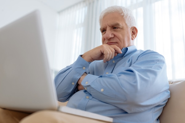 what's that sound coming from my furnace?, elderly man sitting on the couch watching something on his laptop